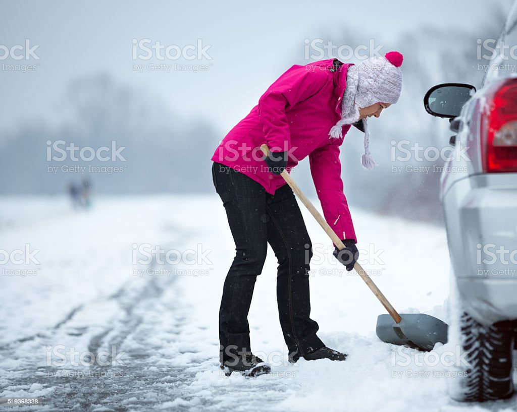 woman cleaning snow around her car stock photo
