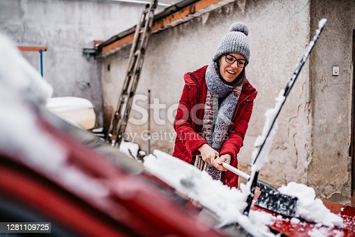 Young woman cleaning snow off her car in backyard.