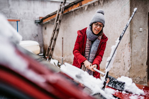Woman cleaning snow off her car Young woman cleaning snow off her car in backyard. image stock pictures, royalty-free photos & images