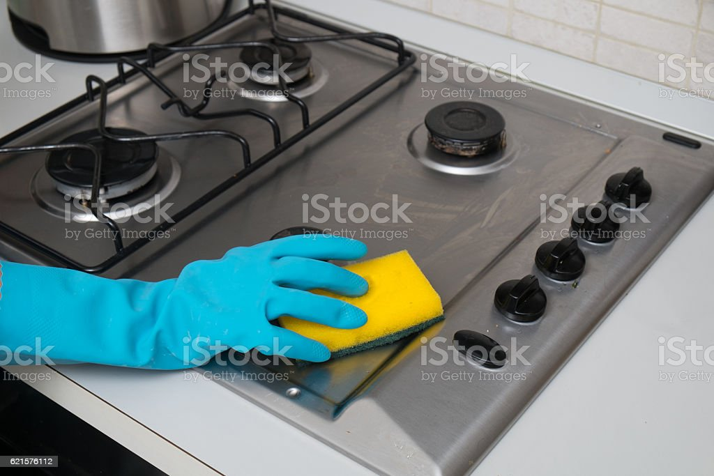 Woman cleaning stainless steel gas surface photo libre de droits