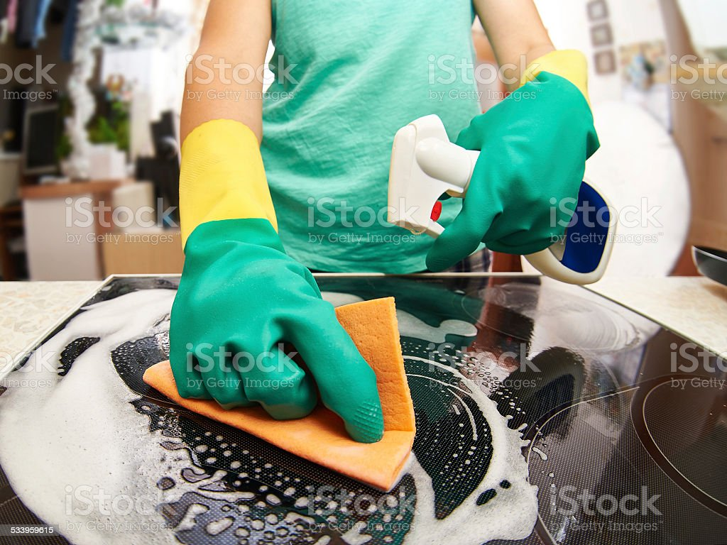 Woman cleaning stove in kitchen stock photo
