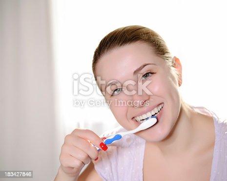 637874676istockphoto woman cleaning teeth 183427846