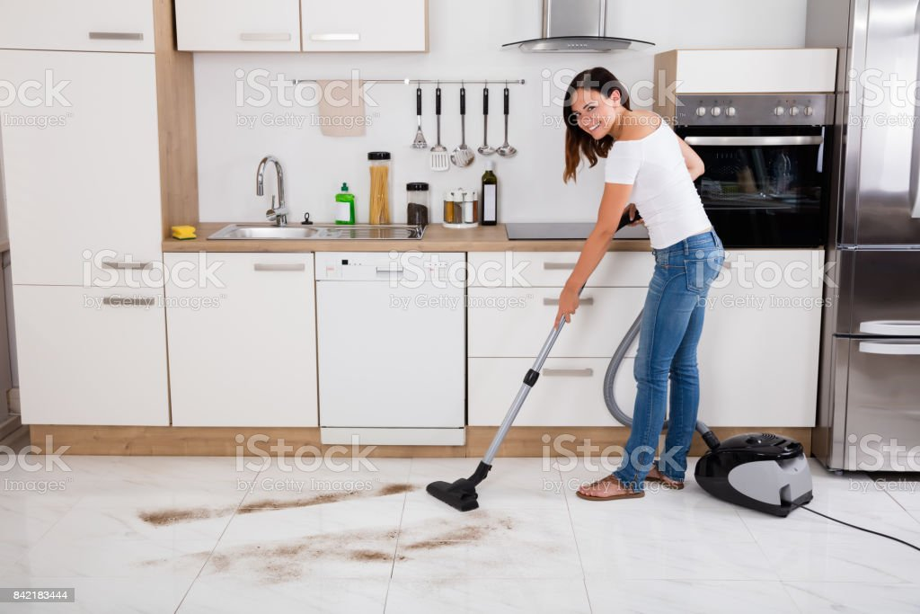 Young Happy Woman Cleaning The Floor Of The Kitchen Using Vacuum...