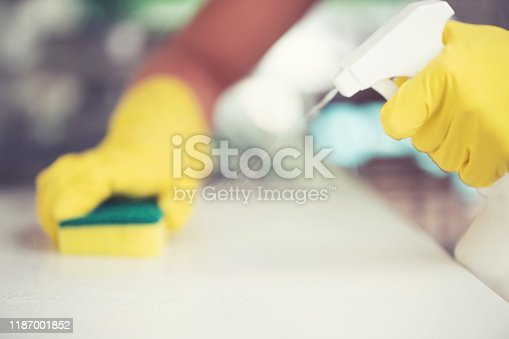 Woman cleaning the kitchen counter with a sponge and spray bottle. She is wearing washing up gloves. Close up