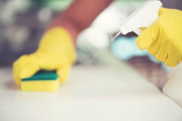 Frau reinigt die Küchentheke mit einem Schwamm und Sprühflasche. – Foto