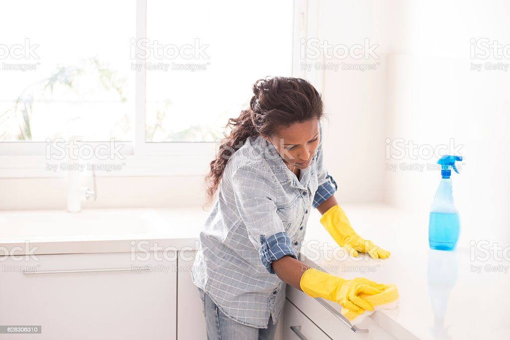 Woman cleaning the kitchen. stock photo