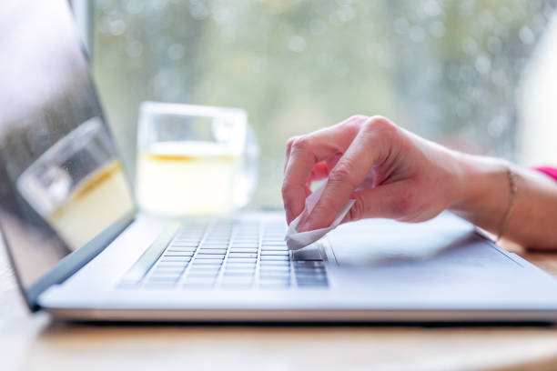 Woman cleaning the laptop keyboard with antibacterial white tissue or disposable wipes stock photo