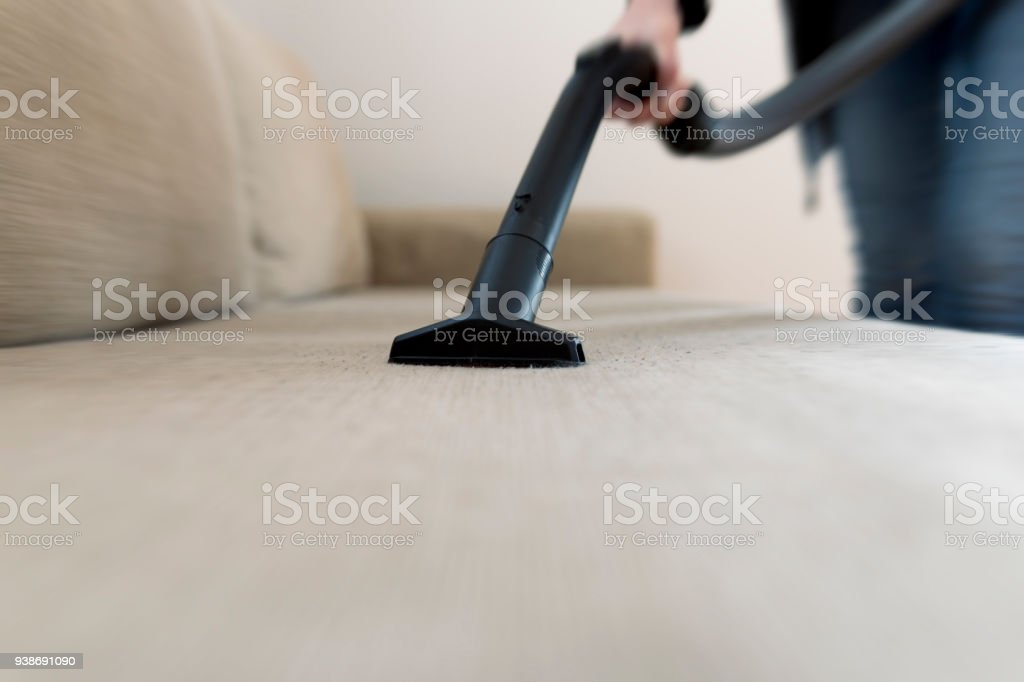 Woman Cleaning The Sofa, Couch With Vacuum Cleaner Royalty Free Stock Photo