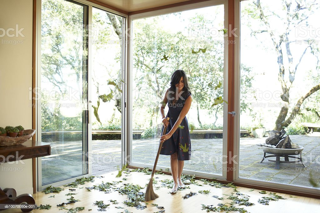 Woman cleaning up fallen leaves on floor, smiling royalty-free stock photo