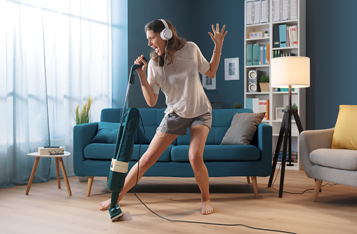 Cheerful woman cleaning up her home and singing, she is using the vacuum cleaner as a microphone
