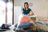 istock Woman cleaning up the closet and sorting clothes in vacuum bags 1220442486