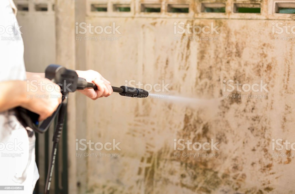 Woman cleaning  waill with high pressure water jet stock photo
