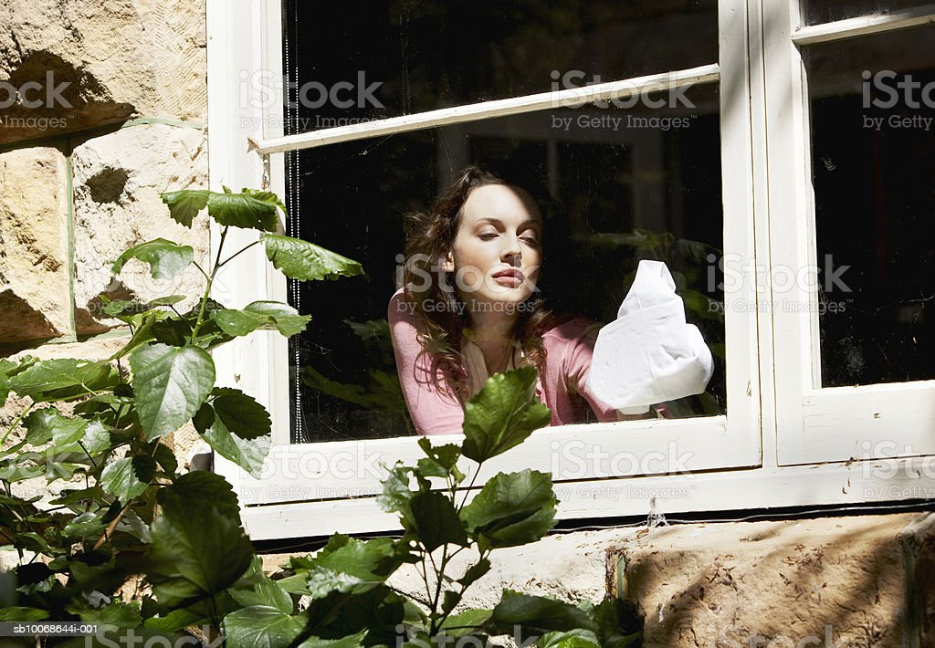 Woman cleaning window inside house, view from outside 免版稅 stock photo
