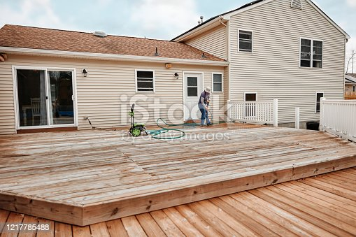 Latin woman cleaning wooden terrace with a high water pressure cleaner.