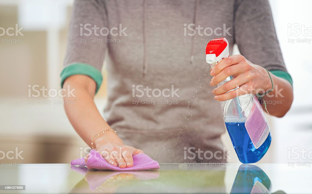 Woman cleans a glass table with a spray stock photo