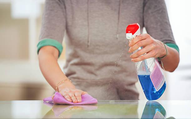 frau reinigt einen glastisch mit einem spray - glaswaschtisch stock-fotos und bilder