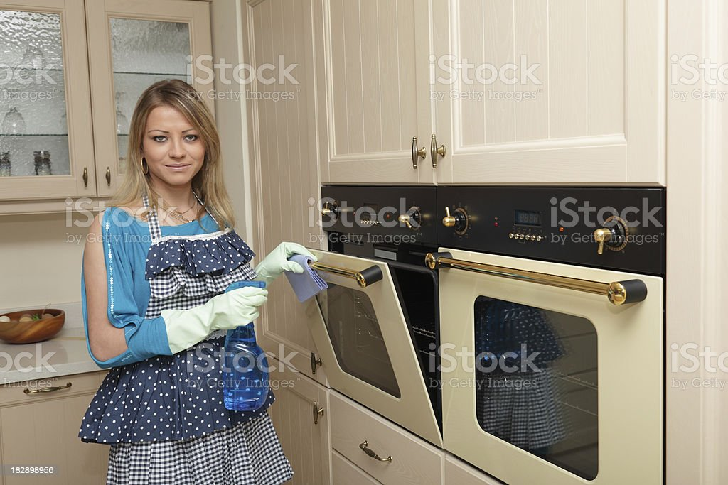 Woman cleans oven in the kitchen royalty-free stock photo