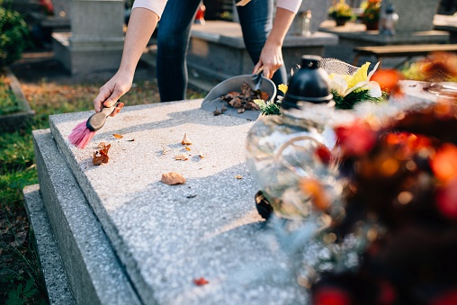 Woman cleans the grave.