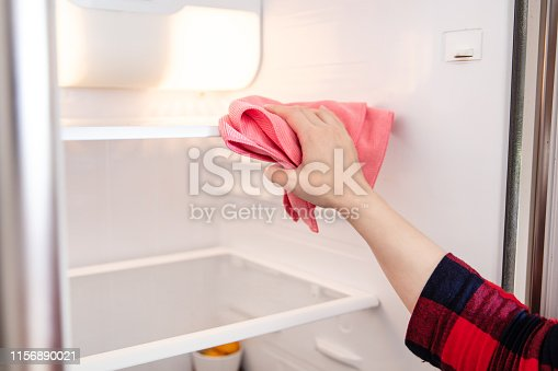 istock Woman cleans up the shelves in the fridge with pink cloth. 1156890021