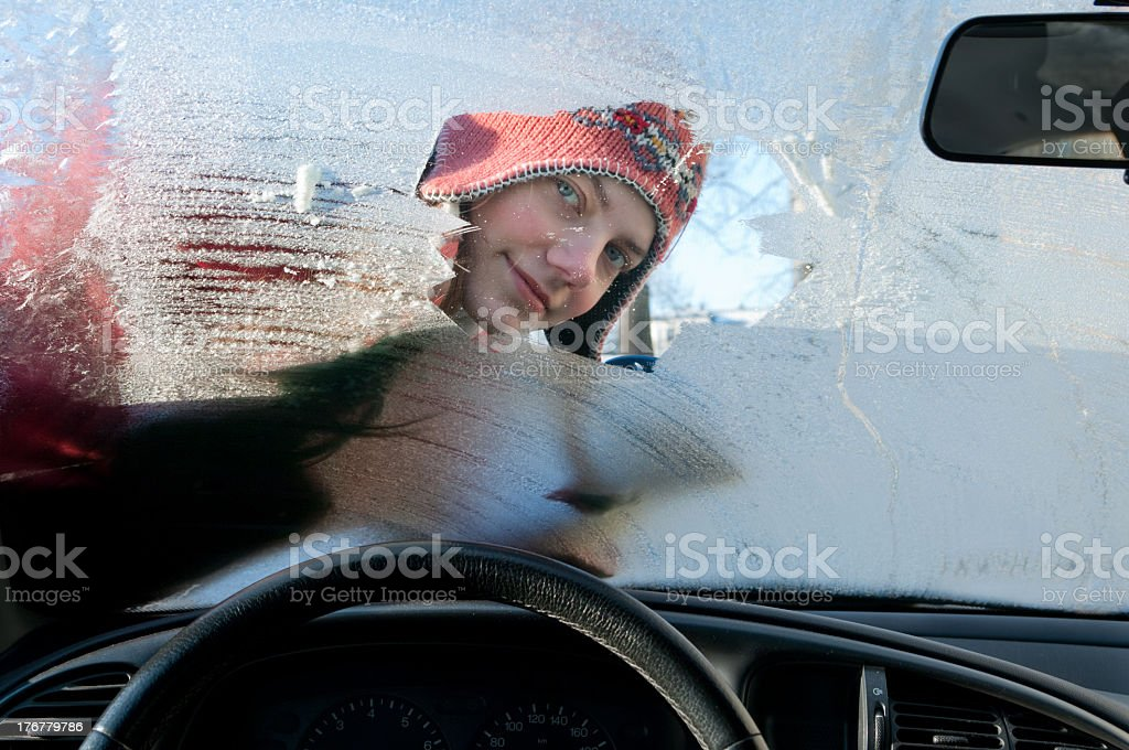 Woman clearing ice off the windshield of a car stock photo