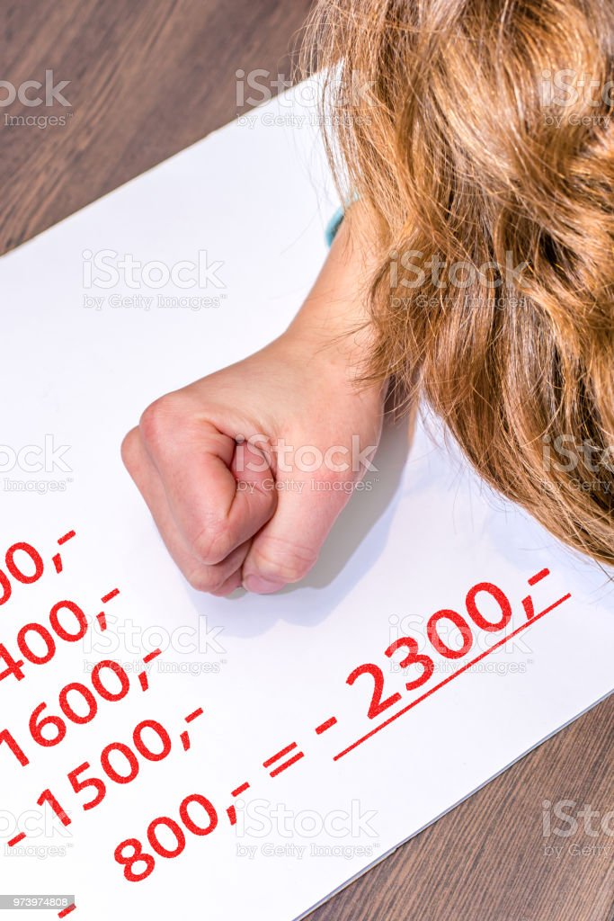 Woman clenches her hand desperately because of the negative figures in portrait format stock photo