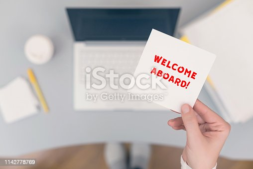 Woman clerk sitting holding note paper sticker with welcome aboard phrase. Business concept. Concept.