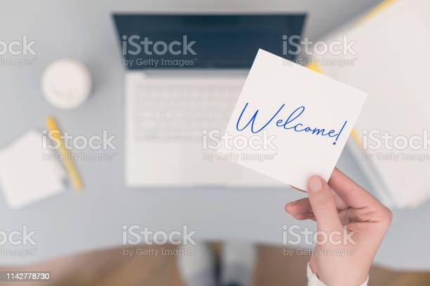 Woman clerk sitting holding note paper sticker with welcome word picture id1142778730?b=1&k=6&m=1142778730&s=612x612&h=iar4njg6blaph3ofns4nmf9n hjianz6va mufe3itm=