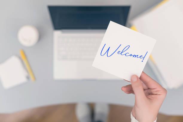 mujer empleada sentada sosteniendo la etiqueta adhesiva del papel de la nota con la palabra de bienvenida. concepto de negocio. concepto. - miembro parte del cuerpo fotografías e imágenes de stock