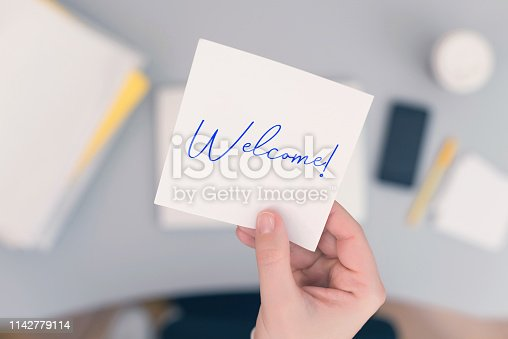 Woman clerk sitting holding note paper sticker with Welcome word. Business concept. Concept.