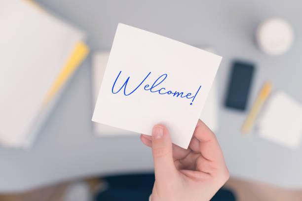 mujer secretario sentado sosteniendo nota pegatina de papel con palabra de bienvenida. concepto de negocio. concepto. - saludar fotografías e imágenes de stock