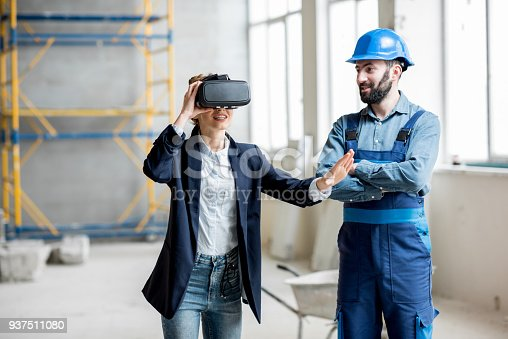 534196421istockphoto Woman client wearing VR glasses at the construction site 937511080