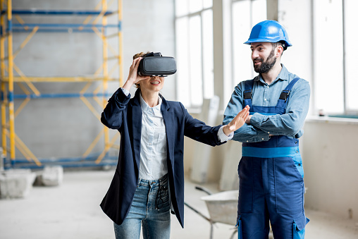 istock Woman client wearing VR glasses at the construction site 937511080