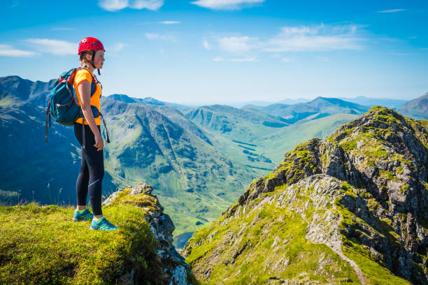 woman climber on mountain ridge overlooking glen coe highlands scotland - nature travel stock photos and pictures
