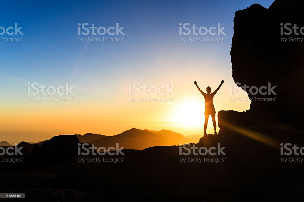 Woman climber success silhouette in mountains, ocean and sunset stock photo