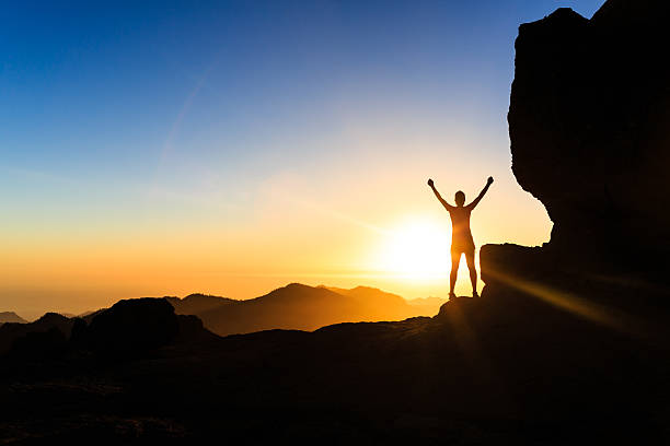 woman climber success silhouette in mountains, ocean and sunset - conquering adversity stock photos and pictures