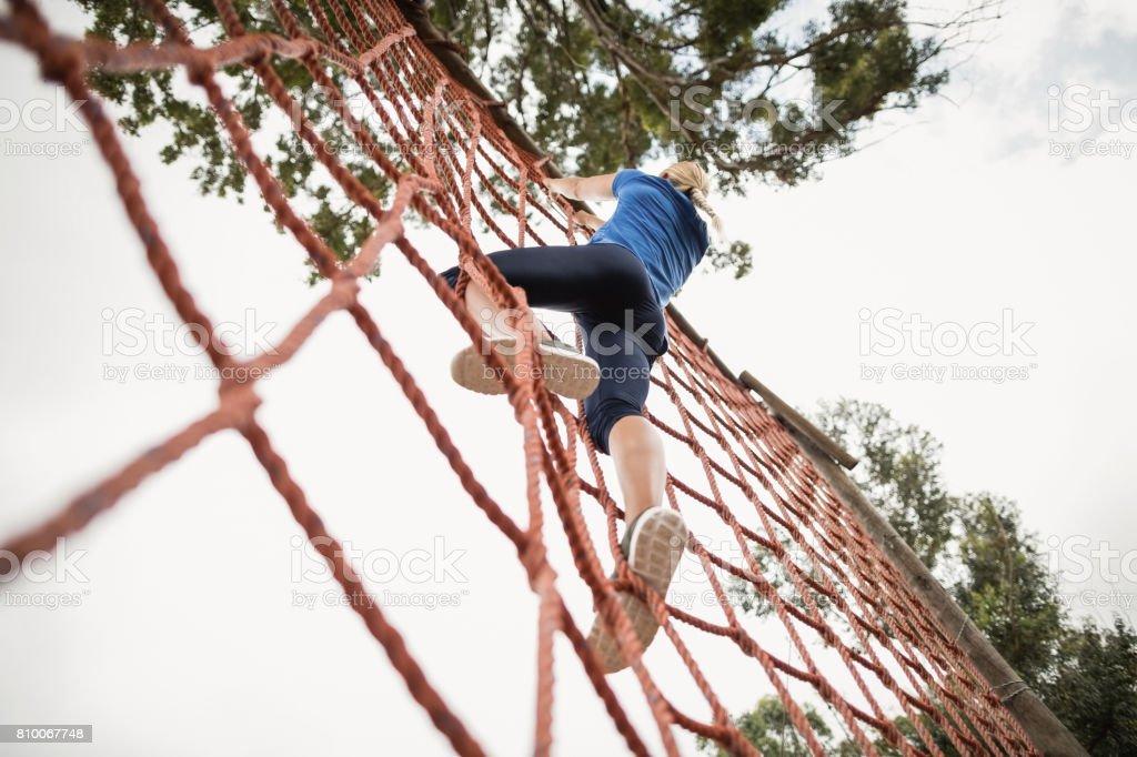 Frau, die ein Netz während der Hindernis-Parcours klettern – Foto