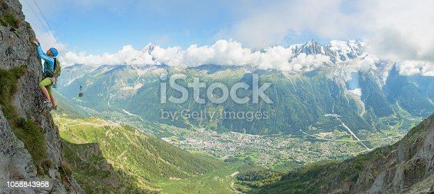 Young woman climbing a rock wall in Chamonix Mont Blanc