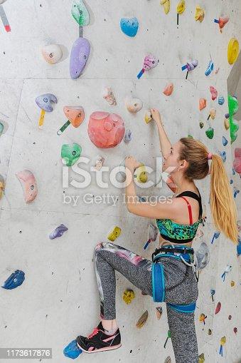 Woman climbing on climbing wall.