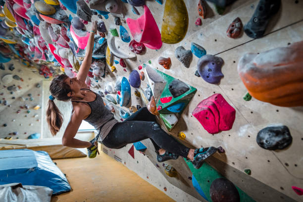 Woman climbing on climbing wall Woman climbing on climbing wall. Climbing gym. image stock pictures, royalty-free photos & images
