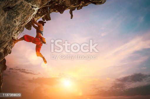 Athletic Woman climbing on overhanging cliff rock with colorful sunset sky background