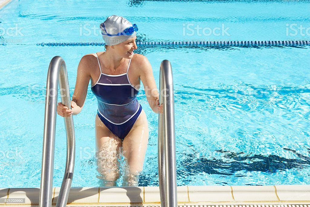 Woman climbing out of swimming pool stock photo