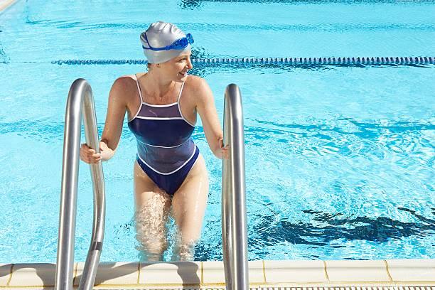 frau klettern auf swimmingpool - pool schritte stock-fotos und bilder