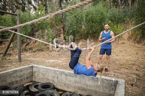 istock Woman climbing rope during obstacle course training 810070744