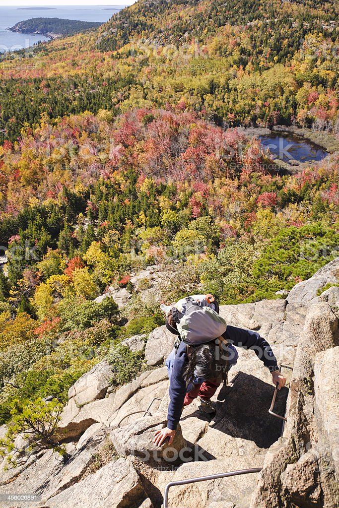 Woman climbing The Beehive, Acadia National Park, in Autumn stock photo