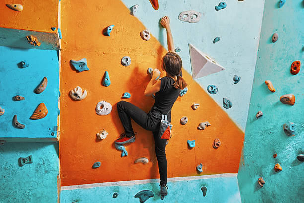 woman climbing up on practice wall - clambering stock photos and pictures