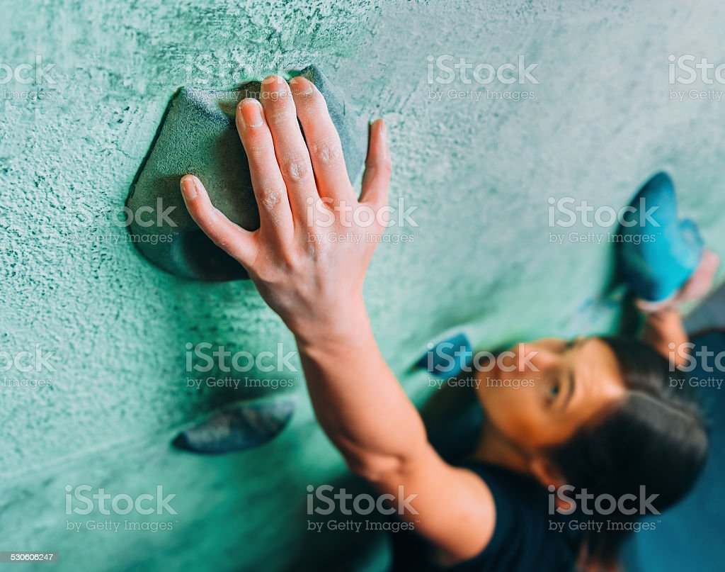 Woman climbing up on wall in gym stock photo