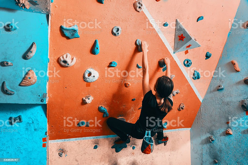 Woman climbing up on wall indoors stock photo