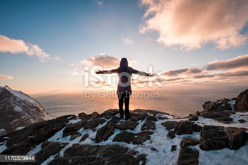 Woman climbing with raised hand on rock mountain at sunset