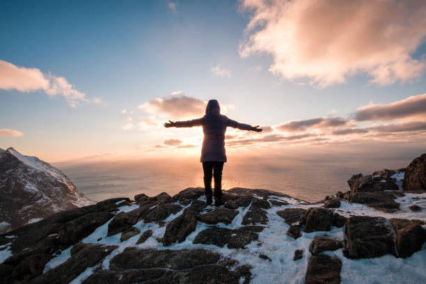 Woman climbing with raised hand on mountain at sunset stock photo