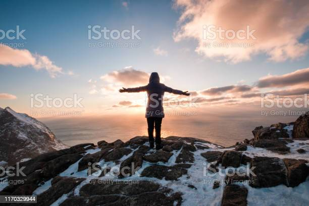 Photo of Woman climbing with raised hand on mountain at sunset